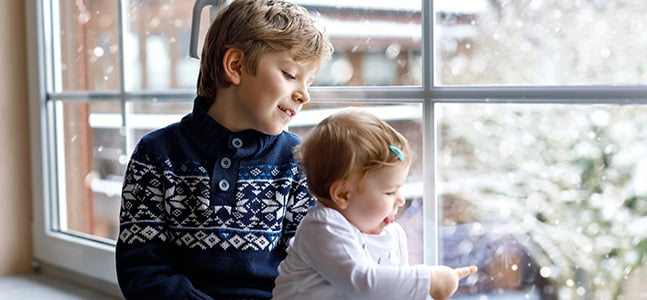 Bild: zwei Kinder im Winter am Fenster